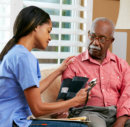 old man assisted by the nurse by getting his blood pressure